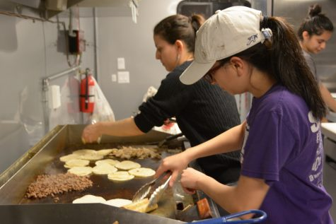 Laura Martinez (right) and  sister Dulce Martinez (left) prepare food for an order. Laura Martinez owns a taco food truck with her husband and has used her business as a means to support not only herself but her family as well.