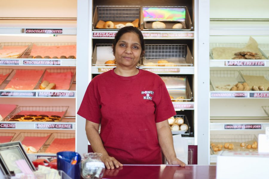 Dipti+Patel+stands+behind+the+counter+of+her+Donut+King+shop+on+Lindsey+Street+after+the+morning+rush.+She+and+her+husband%2C+Sanjay+Patel%2C+bought+the+shop+in+1994%2C+when+it+was+a+Dunkin%E2%80%99+Donuts+franchise.++Megan+Ross+%2F+The+Daily