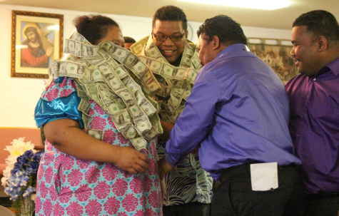 Pastor Alfred Alfred stands with a Marshallese woman during the United Church of Christ Sunday service on April 2, where men and women approach the two with taped dollar bills to place around their necks. The tradition is symbolic for Alfred's reputation within the community.