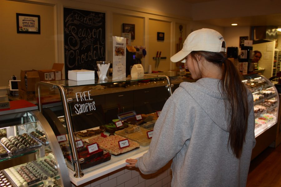 University of Oklahoma student Peyton Brougher purchases a dessert from Apple Tree Chocolates on Campus Corner in Norman. Apple Tree Chocolates offers chocolate-dipped fruit, fudge, baked goods and much more.