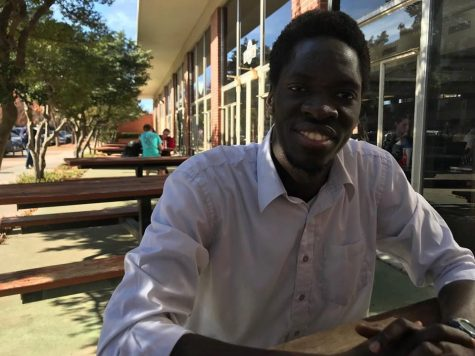 Robert Bob Okello, junior from Uganda and president of The United World, sits outside of Cate Center and discusses his views on the declining number of international student enrollments at The University of Oklahoma.