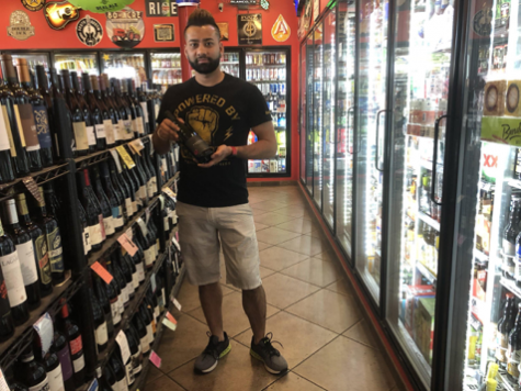 Daniel Joshi, founder of Rosedale Market, holds his favorite  wine selection from the store inventory on March 22, 2018,  in Austin, Texas. The corner store has stocked over 900  variations of wine and champagne.