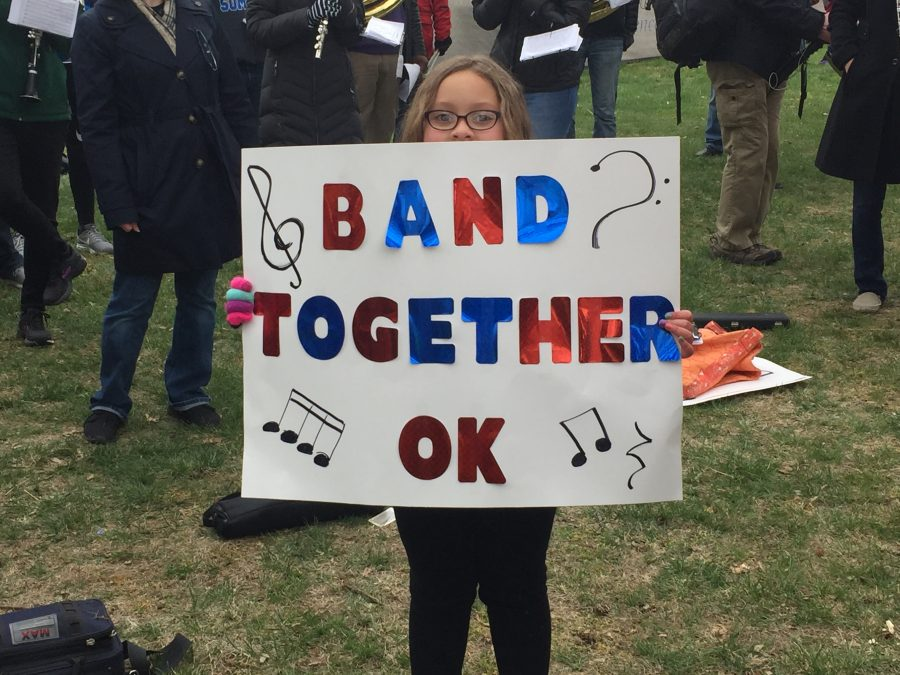 A young girl holds a sign in support of the