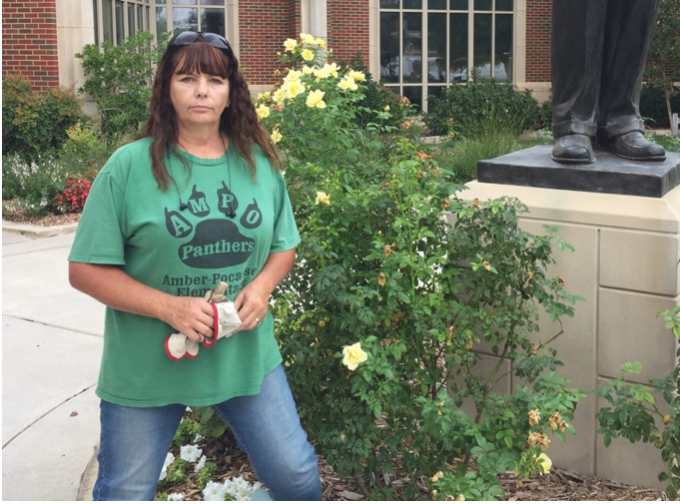 University of Oklahoma landscaping specialist Tammie Mitchell stands in front of surviving roses in the Gaylord courtyard on Sept. 10. Many of OU campus roses have been killed by a virus called Rose Rosette or witches' broom.