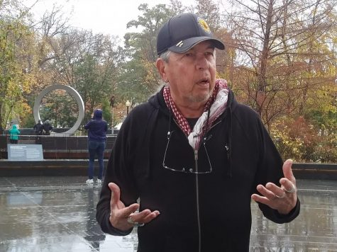 Harvey Pratt, designer of the National Native American Veteran Memorial, speaks with reporters at the Museum of the American Indian. The memorial can be seen in the distance over his shoulder. Photo courtesy Gaylord News / Jessie Christopher Smith