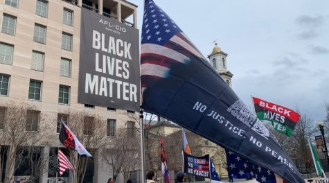 BLM protestors hold flags up against the fence protecting the White House in Black Lives Matter Plaza. (By Skylar Tallal/Gaylord News)