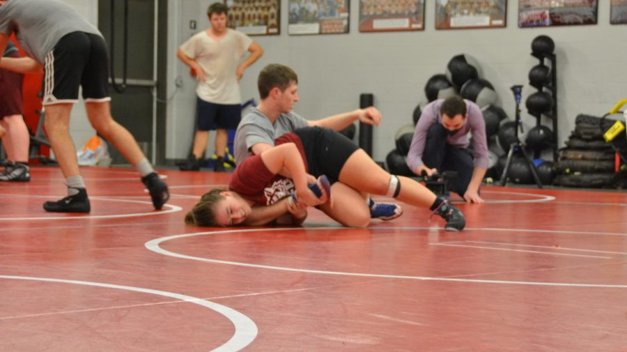 Rayleigh Fisher, a 16-year-old girl, practices on Tuesday at Tuttle High School to become the first girl's state champion in the 147 pound weight class.