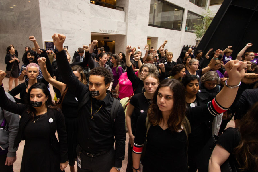 Protesters in the Hart Senate Office Building silently held up their hands in solidarity during Christine Blasey Ford's testimony before the Senate Judiciary Committee. (Megan Ross / Gaylord News)