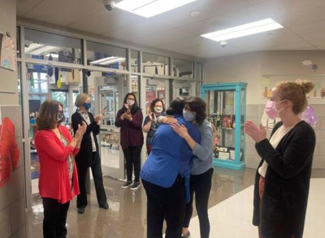 Cafeteria manager Yanet Viamontes hugs library assistant Mais Shalabi in the hallway at Prairie Vale Elementary School. The staff celebrated Viamontes with chants and applause after she passed her citizenship exam. (Photo provided by Prairie Vale Elmentary School)
