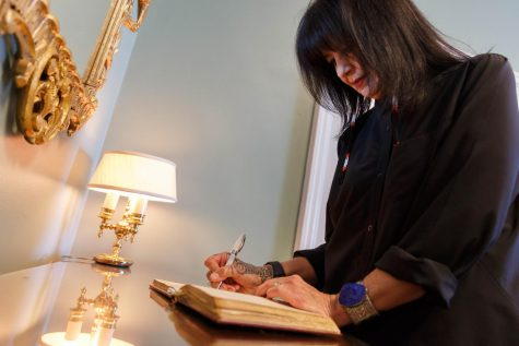 -Joy Harjo signs into the Poetry and Literature Centers historic guest book as the nations 23rd poet laureate. (Shawn Miller/Library of Congress)