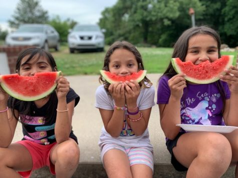 Kim Duncan's three adopted daughters, from left, Shalyn, Shyanne and Shelbi, sit smiling with their watermelon in the summer heat. (Photo provided)