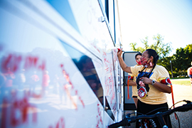 LoVina Louie, the wife of MMIW Bike Run USA organizer Duane Garvais-Lawrence, adds names to the side of the motor home that carried them on the trip. One goal of the trip was to raise $186,090 - representing the amount of women and children missing - to support an MMIW center in Seattle. (Diannie Chavez/Cronkite News)